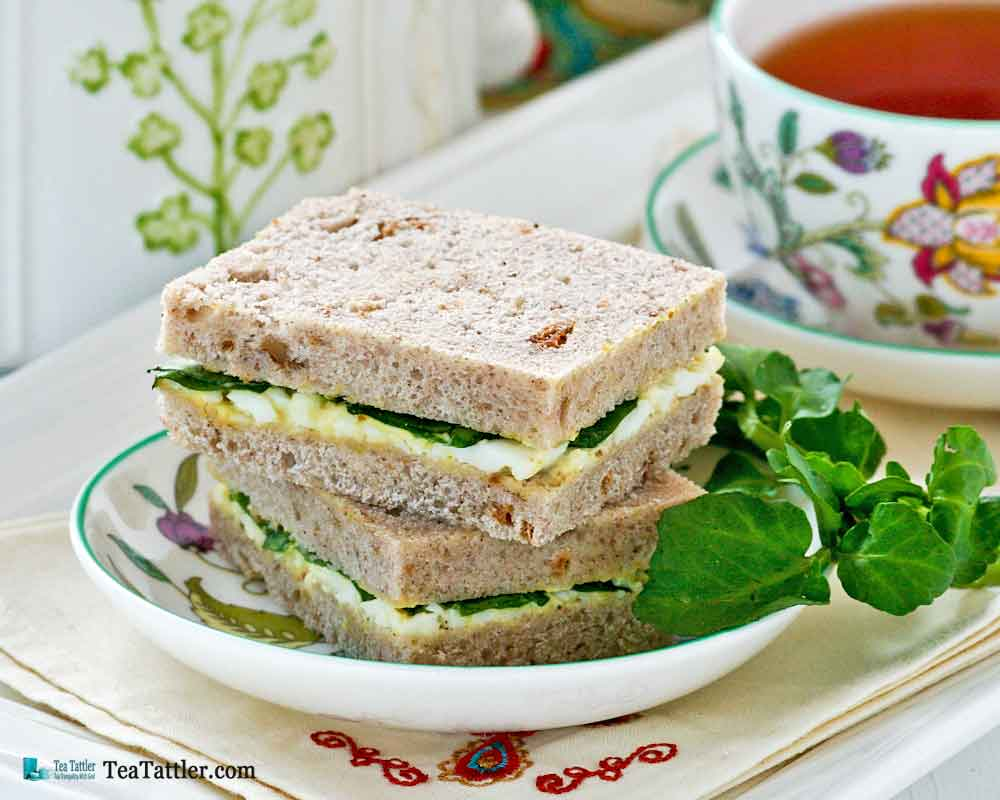 Dainty Egg and Watercress Sandwiches with hard cooked eggs and mayonnaise. Watercress provides a slightly peppery bite to the sandwiches. | TeaTattler.com #watercresseggsandwiches #eggsandwiches