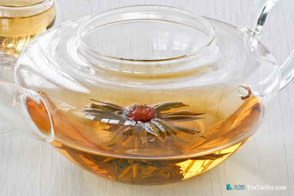 1000 Day Flower Tea is a hand tied tea ball with amaranth blossom in the center. It has a pale golden infusion and light floral notes. | TeaTattler.com #floweringtea #bloomingtea #greentea